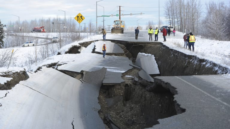 Workers inspect an off-ramp that collapsed during a morning earthquake in Anchorage, Alaska.