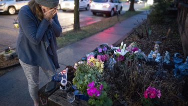 Rene Norton, a friend and neighbour of Damond, wipes away tears at a memorial near the alley where she was killed.