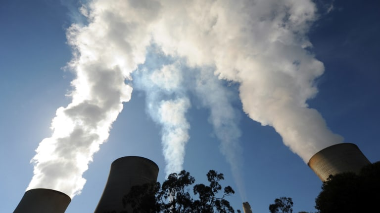Steam billows from the cooling towers of a coal-fired power station.