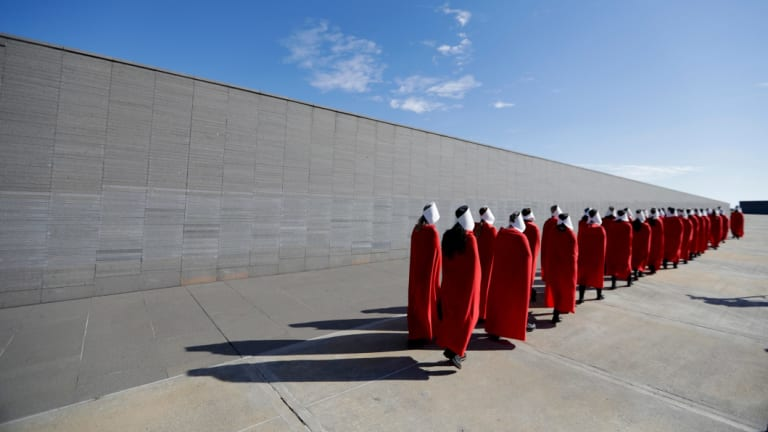 Pro-choice activists wear costumes from the Handmaid's Tale, as they march through Remembrance Park, created to honour the victims of state terrorism and lists the names of those who disappeared during Argentina's last military dictatorship, in Buenos Aires.
