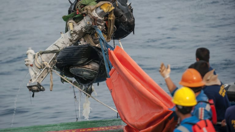 Rescuers use crane to retrieve part of the landing gears of the crashed Lion Air jet.