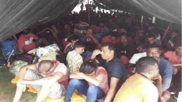 This photo, released by the Royal Malaysian Police, shows illegal migrants on a rusty tanker near Kota Tinggi in Johor state, Malaysia.