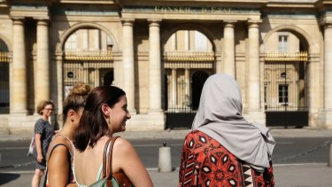 A woman wearing a Muslim headscarf, right, and who refused to be identified, stands outside the Conseil d'Etat, France's top administrative court, in Paris. The court overturned a town burkini ban in 2016.