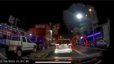 A screenshot from the dashcam footage. A group of people are seen outside the boxing venue.