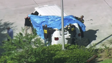 FBI agents cover a van parked in Plantation, Florida.