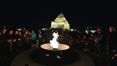 People gather at The Eternal Flame for Anzac Day dawn service.
