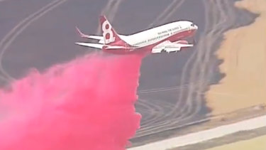 An air tanker drops pink fire retardant over properties in South Australia.
