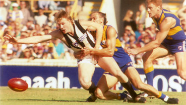 Nathan Buckley is tackled by Peter Matera during the 1994 qualifying final in Perth.