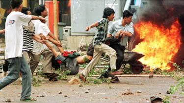 Student protesters carry a man shot by police during riots on May 14, 1998.