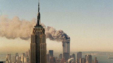The twin towers of the World Trade Center burn behind the Empire State Building on September 11, 2001.