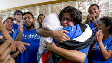 Rashida Tlaib embraces her mother Fatima Elabed, who wears a Palestinian flag across her shoulders, in Detroit after Tlaib won the Democratic primary race on August 7.