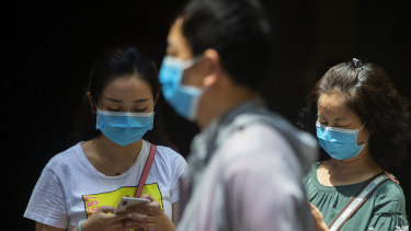 People wearing masks in Sydney CBD as health authorities work to contain an outbreak of COVID-19.