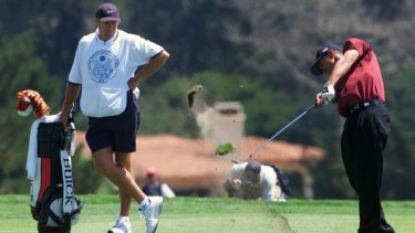 Steve Williams watches on as Tiger Woods hits on the 11th green at Pebble Beach in 2000.