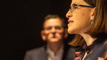 Daniel Andrews watches his then health minister Jenny Mikakos at the podium.