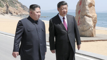 North Korean leader Kim Jong-un walks with Chinese President Xi Jinping during a meeting in Dalian.