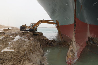 A backhoe tries to dig out the keel of the Ever Given.