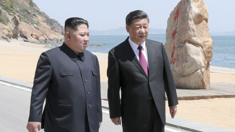 Chinese President Xi Jinping, walks with North Korean leader Kim Jong-un during a meeting in Dalian.
