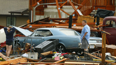 A man and woman inspect the damage to their home and classic cars after a tornado hit Kansas.