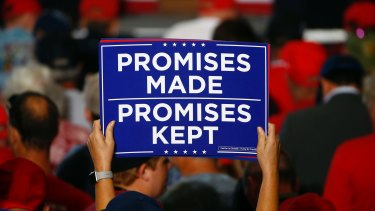 Promises to keep - even if they're not based in reality. Supporters hold up signs as the wait to hear President Donald Trump speak at a campaign rally in Florida in November.