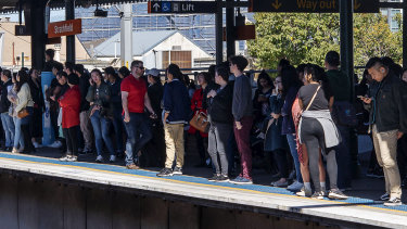 Travellers wait for trains at Strathfield station on Saturday.