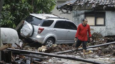 A man walks near debris at a tsunami-ravaged area in Carita, Indonesia.