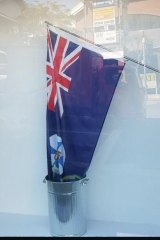 The Queensland flag being lowered into a rubbish tin of bleach symbolises the state losing its life, the artists say.