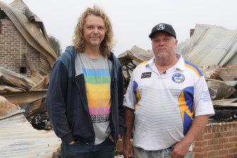 Kyle Moser, left, and his partner David Wilson, in front of the ruins of their Cobargo home.