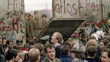 West Berliners watch East German border guards demolishing a section of the wall on November 11, 1989.