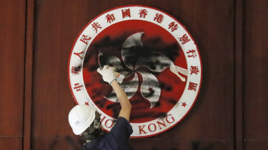 A protester defaces the Hong Kong emblem after breaking into the Legislative Council building on July 1, 2019. Protesters took over the legislature's main building, tearing down portraits of legislative leaders and spray painting pro-democracy slogans on the walls of the main chamber.