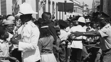 Police attempted to control the crowd as they struggled to get a closer look at Britain's Queen Elizabeth and Prince Philip on their arrival in Trafalgar Square, Bridgetown in Barbados in 1966.