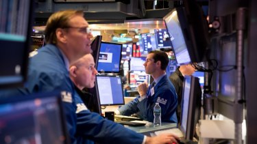 Traders on the floor of the New York Stock Exchange. Stocks have surged on the news of the partial trade deal.