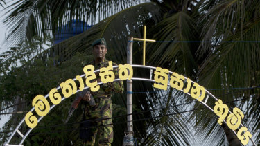 An officer of the Sri Lankan Special Task Force stands guard atop a building as funerals of Easter Sunday bomb blast victims take place at the Methodist burial ground in Negombo.