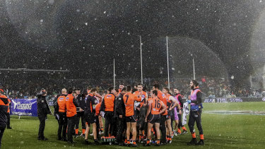 Snow falls on the ground during the game between GWS and Hawthorn in Canberra.