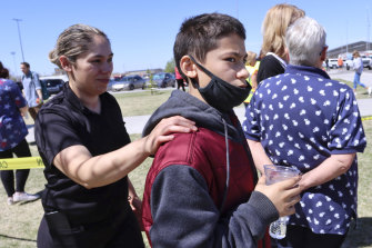 Adela Rodriguez with her son, Yandel Rodriguez, 12, after they were evacuated following a shooting at the nearby Rigby Middle School on Thursday.