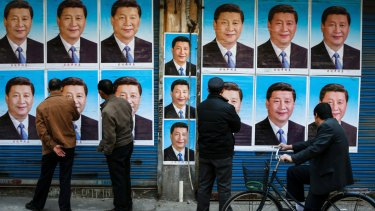 People look at a building covered in posters of Chinese President Xi Jinping in Shanghai.