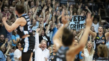 Canberra Capitals coaches and players cheer as they realise their dream of winning the championship.