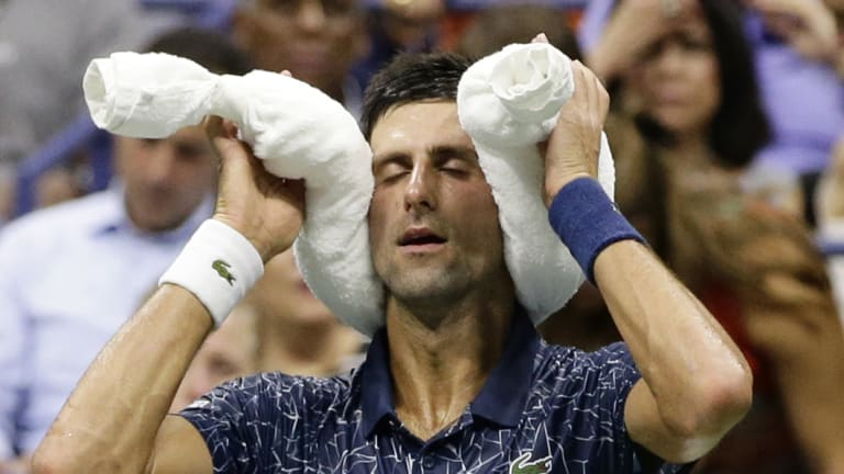 Hot and humid: Novak Djokovic at a change of ends with bags of ice.