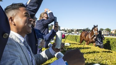 Punters celebrate as horses return to their raceday stalls after The Everest.