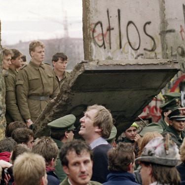 West Berliners watch East German border guards open up a new crossing point in the Berlin Wall in 1989.