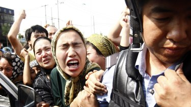 An angry crowd of Uighur Muslims jostle police during protests in Urumqi in 2009.
