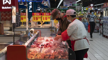 A saleswoman helps a customer choose meat at a Carrefour Superstore in Beijing.