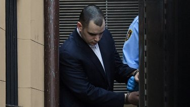 Mathew Flame is led away from court during his trial.