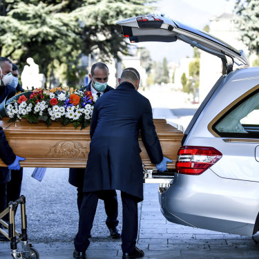 Undertakers carry a coffin out of a hearse at Bergamo's cemetery, northern Italy.