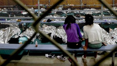 Two girls watch television as others around them sleep in holding cells where hundreds of mostly Central American immigrant children wait to be processed at the US Border Protection Placement Centre in Nogales, Arizona, in 2014.