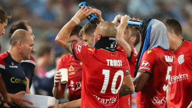 Adelaide players take a drinks break during the match with Sydney FC on Saturday night.