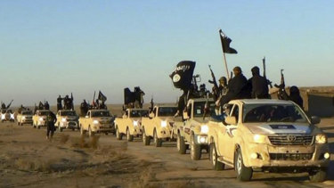 In this undated file photo released online in the summer of 2014 on a militant social media account,  militants of the Islamic State group hold up their weapons and wave its flags on their vehicles in a convoy on a road leading to Iraq, in Raqqa, Syria.