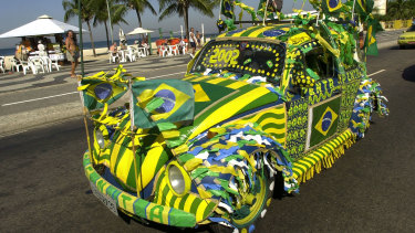 A Volkswagen Beetle, known as Fusca in Brazil, drives around Rio de Janeiro painted in the Brazilian colours during the 2002 FIFA World Cup.