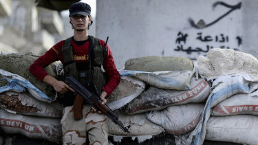 A Syrian opposition fighter stands at a checkpoint in the north-western city of Idlib, Syria, late on Saturday.