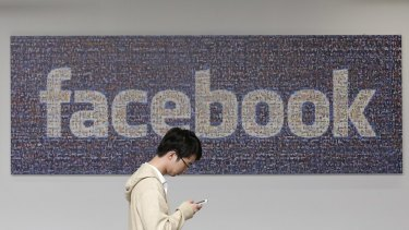 A man walks past a Facebook sign in an office on the Facebook campus in Menlo Park, California.