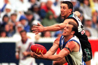 Darren Mead, left, in action against Wayne Carey in 1999.